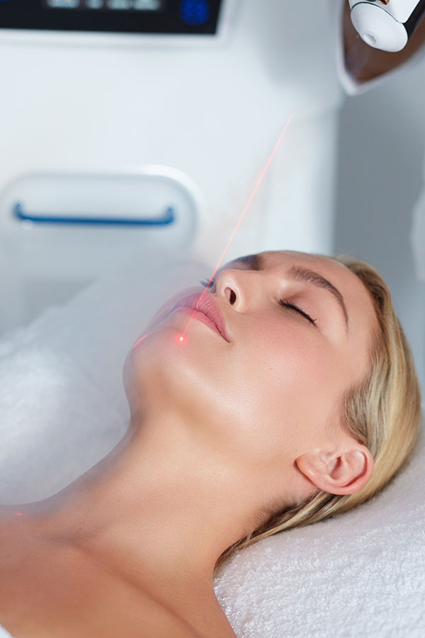 Woman getting Fire and Ice Laser Facial with cryogenic air treatment to improve skin tone at Gleam Medical Spa in Denver, Colorado
