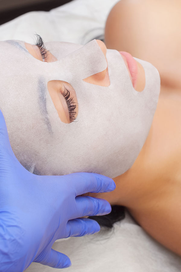 Woman getting gel sheet face mask as part of Fire and Ice Laser Facial treatment at Gleam Medical Spa in Denver, Colorado