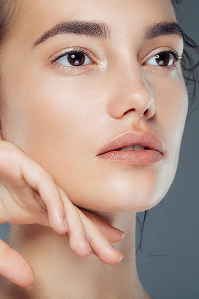Woman with youthful skin after exosome microneedling treatment at Gleam Medical Spa